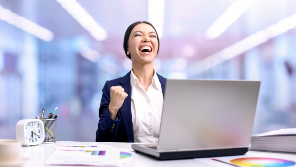 woman celebrating in front of a laptop