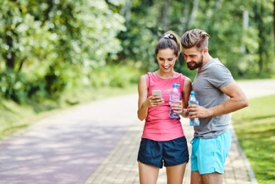 Two millennials looking at cell phone while exercising