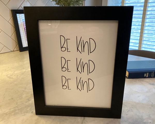 "framed photo saying ""be kind"""