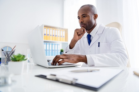 Doctor looking at computer completing physician bio survey