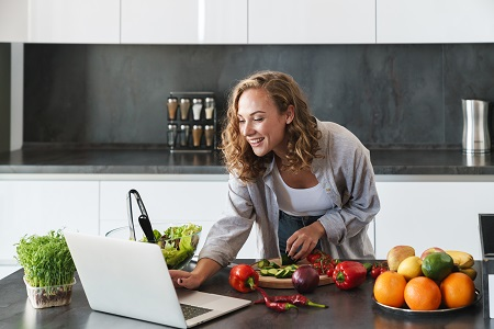 woman cooking healthy while looking at laptop