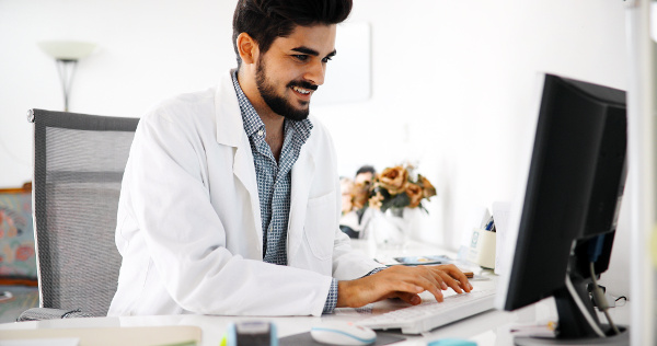 Doctor typing out an email to a patient