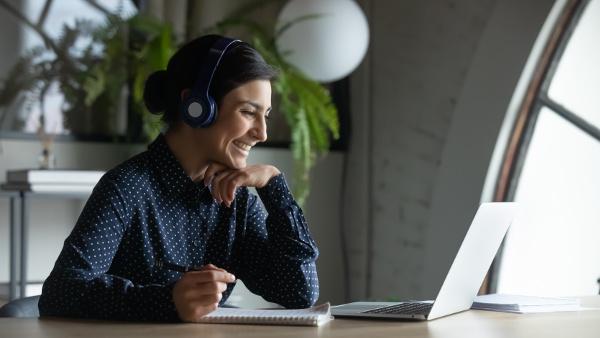 woman watching a webinar taking notes